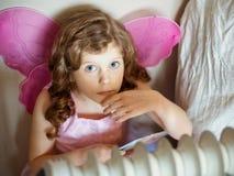 Liten flicka som ha på sig fjärilen, påskyndar arkivfoto