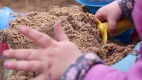 Liten flicka som har gyckel med en sand