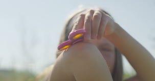 Liten flicka som har gyckel med grejspinnaresammanträde på grönt gräs arkivfilmer