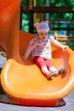 Liten flicka som har gyckel på en glidbana Arkivfoton