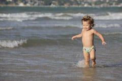 Liten flicka som har gyckel på stranden royaltyfri foto