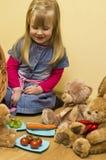 Liten flicka som har lunch med hennes välfyllda leksaker Arkivfoto