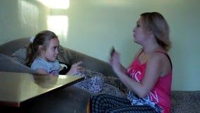 Liten flicka som heatedly spelar med den hemmastadda telefonen Beroende för barn` s på grejer Mamman grälar på dottern för att sp arkivfilmer