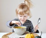Liten flicka som hemma äter pumpaKräm-soppa Royaltyfri Fotografi