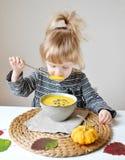 Liten flicka som hemma äter pumpaKräm-soppa Royaltyfria Foton