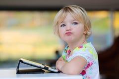 Liten flicka som hemma använder minnestavlaPC Royaltyfria Bilder