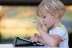 Liten flicka som hemma använder minnestavlaPC Arkivfoto