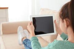 Liten flicka som hemma använder video pratstund på minnestavlan arkivfoto