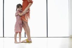 Liten flicka som hemma kramar modern arkivbilder