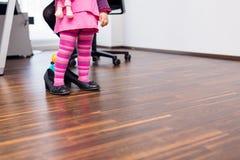 Liten flicka som i regeringsställning bär stora skor Arkivbilder