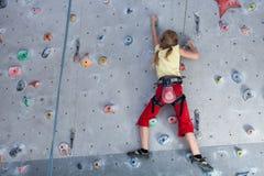 Liten flicka som inomhus klättrar en vaggavägg royaltyfri bild