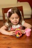 Liten flicka som inomhus spelar med lera Fotografering för Bildbyråer