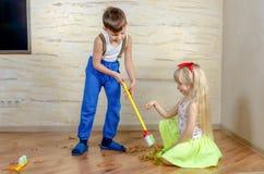 Liten flicka som instruerar hennes broder What att göra ren Fotografering för Bildbyråer