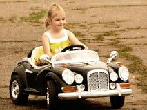 Liten flicka som kör en bil på vägen Arkivbilder