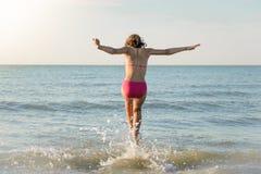 Liten flicka som kör till havet, hopp Fotografering för Bildbyråer
