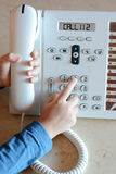 Liten flicka som kallar för hjälp på 112 från landlinetelefonen Royaltyfria Bilder