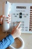 Liten flicka som kallar för hjälp på 112 från landlinetelefonen Royaltyfri Bild