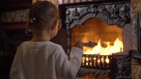 Liten flicka som kastar trän i flamman av spisen stock video