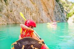 Liten flicka som kayaking på den härliga floden, har gyckel och utomhus tycker om sportar Vattensport och campa gyckel royaltyfri fotografi