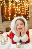Liten flicka som kläs som jultomten av spisen Arkivfoto
