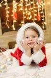 Liten flicka som kläs som jultomten av spisen Royaltyfria Bilder