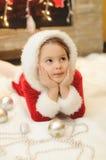 Liten flicka som kläs som jultomten av spisen Royaltyfri Foto