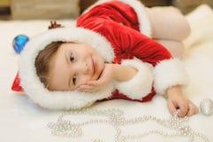 Liten flicka som kläs som jultomten av spisen Arkivbild