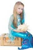 Liten flicka som kläs som mermaid, sitter med snäckskal Fotografering för Bildbyråer