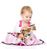Liten flicka som klappar kattungen På vitbakgrund Arkivfoto