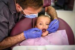 Liten flicka som kontrollerar tänder royaltyfri fotografi