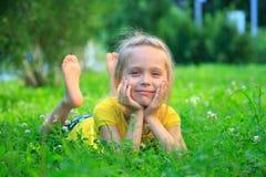 Liten flicka som kopplar av på gräs royaltyfri fotografi