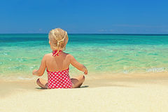 Liten flicka som kopplar av på sandstrandkanten Royaltyfria Foton