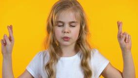 Liten flicka som korsar fingrar och g?r ?nskaen, stark lust, barnslig naivitet arkivfilmer