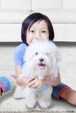 Liten flicka som kramar en maltese hund Arkivbild
