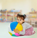 Liten flicka som kramar en stor boll arkivfoto