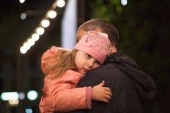 Liten flicka som kramar hennes fader arkivbilder