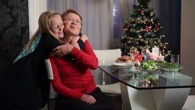 Liten flicka som kramar hennes farmor på jul lager videofilmer