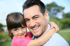 Liten flicka som kramar hennes le fader Arkivfoton