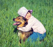 Liten flicka som kramar hunden, Arkivbild