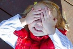 Liten flicka som lägger på jordkläderen henne ögon med båda han Royaltyfria Bilder