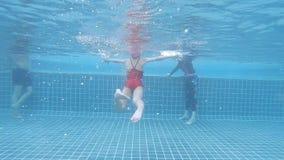 Liten flicka som lär att simma under vattenskott lager videofilmer