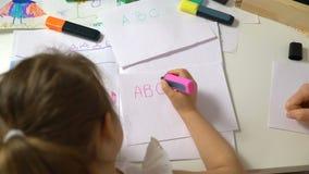 Liten flicka som lär att skriva alfabetet Dockaskott arkivfilmer