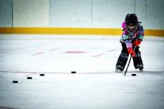 Liten flicka som lär att spela hockey Arkivbild