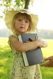 Liten flicka som läser bibeln i natur arkivfoton