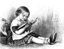Liten flicka som läser en bilderbok Arkivfoto