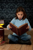 Liten flicka som läser en bok royaltyfria bilder