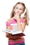 Liten flicka som läser en bok. Arkivbild
