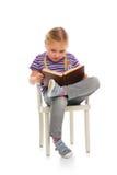 Liten flicka som läser en bok Arkivbild