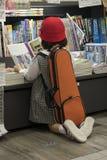 Liten flicka som läser en bok i en japansk bokhandel med ett fiolfall på henne baksida fotografering för bildbyråer