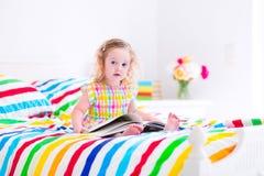 Liten flicka som läser en bok i säng Fotografering för Bildbyråer